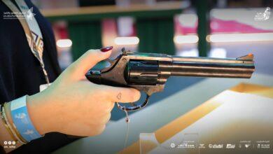 سيدة تجرب استخدام مسدساً في معرض الصقور والصيد في الرياض.